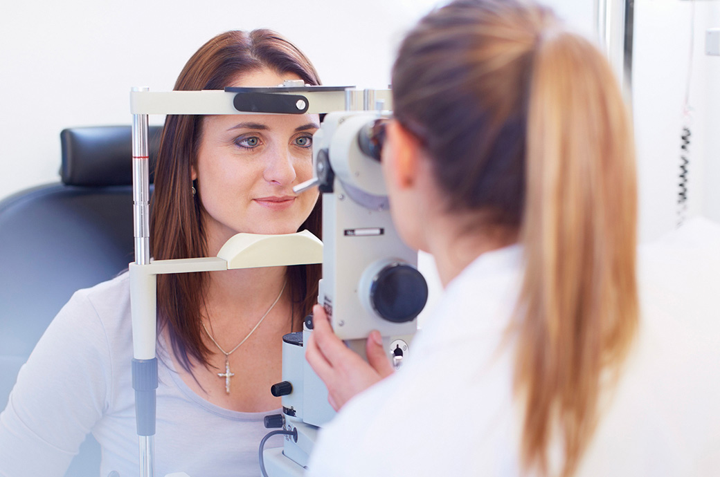 The camera focuses on a young woman looking through a retinal camera as her doctor looks through the other side