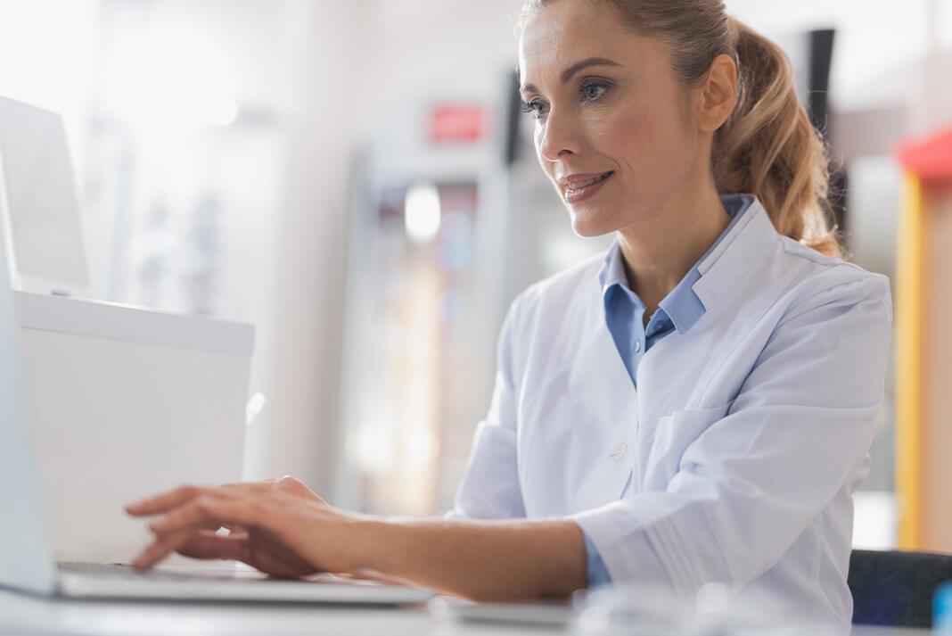 Et bilde av en optiker som sitter ved skrivebordet sitt og bruker en tablett