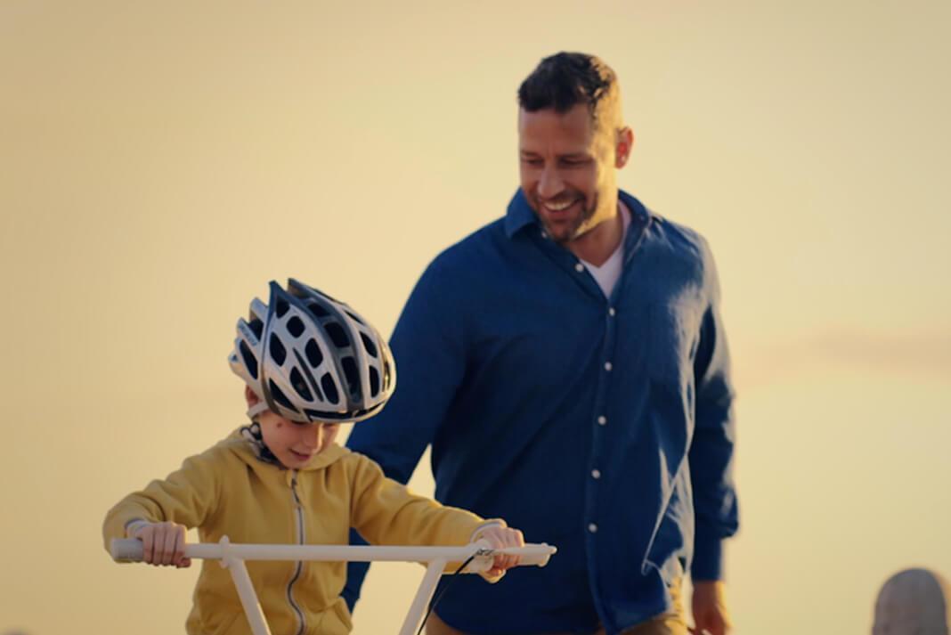 Et bilde av en liten gutt som lærer å sykle med farens hjelp